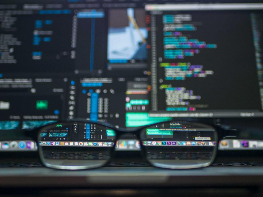 Brille vor Computer mit Programmiersprache
