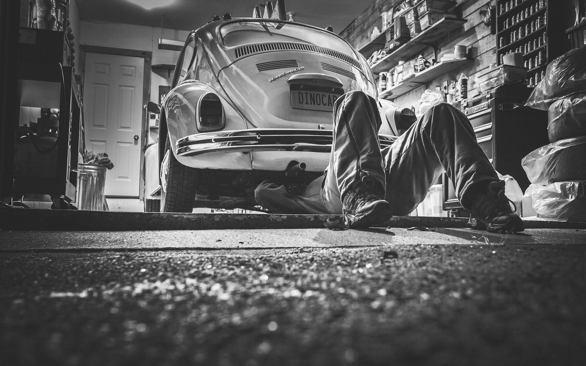 Handwerker liegt unter dem Auto
